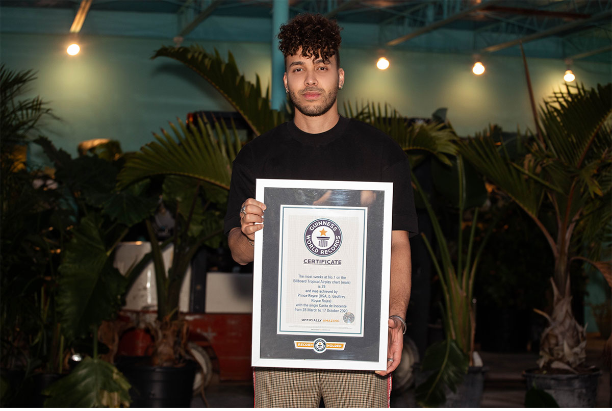 Prince Royce Holding Certificate dark background