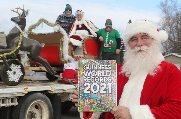 kevin fast holding 2021 book with family in the background in the sleigh